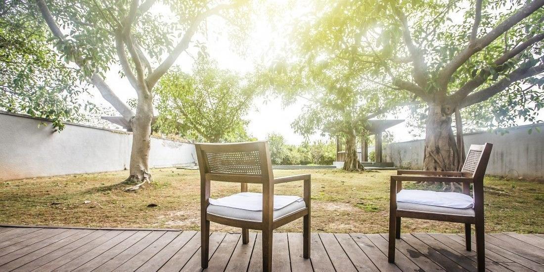 Deck de madeira em meio ao verde cria um espaço aconchegante no quintal (Freepik/Banco de Imagens)