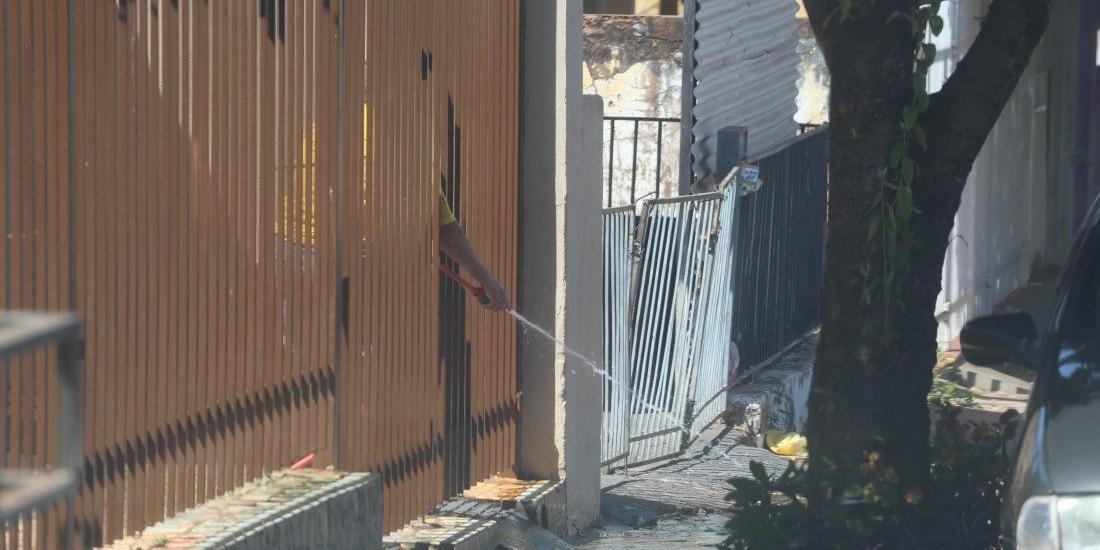 Moradora lava a calçada com mangueira de jardim: em tempos de estiagem, é recomendável evitar a ação (Guilherme Baffi 11/9/2020)